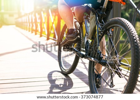 Bicyclist rides on the road in city park. Sunny summer hot day - stock photo