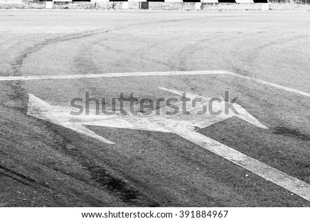bidirectional arrow symbol on a wet asphalt road for the concept of choice. - stock photo