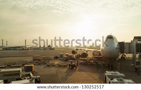 big airplane at airport in beautiful morning light through glass - stock photo