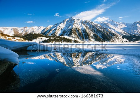 Big Almaty lake on december. Water, ice, mountains and snow. - stock photo