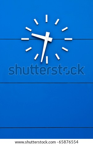 Big analog clock on blue wall - stock photo