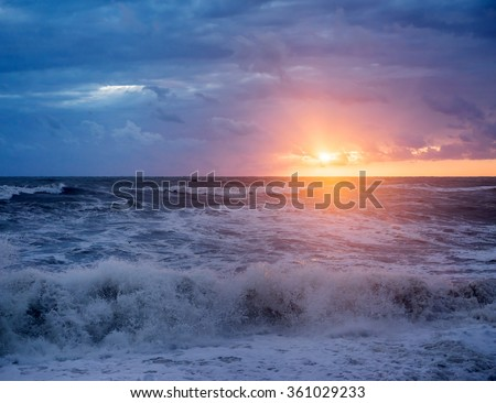 Big and powerful sea waves during the storm in autumn day on background beautiful sunset - stock photo