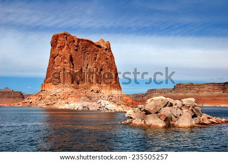 Big and small rocks line the shore of Lake Powell.  Mesas and monoliths dot the landscape. - stock photo