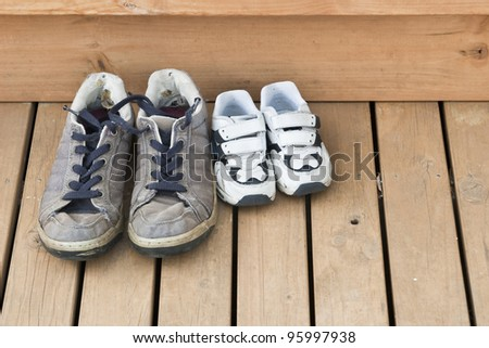 Big and small shoes on the back deck - stock photo
