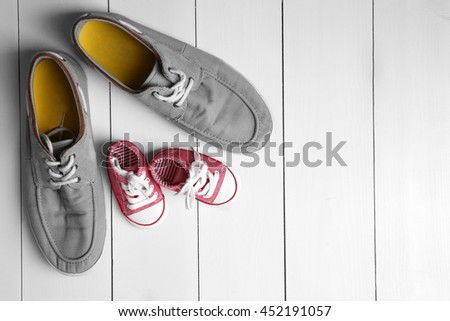 Big and small shoes on wooden background - stock photo