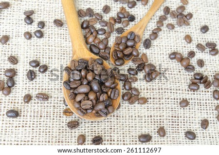 Big and small spoons filled with whole coffee beans on a vintage tablecloth - stock photo