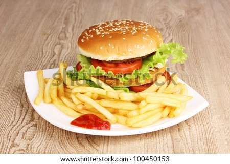 Big and tasty hamburger and fried potatoes on plate on wooden table - stock photo