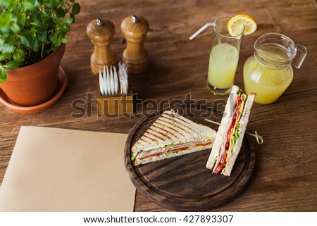 big appetizing sandwich with ham, tomato, lettuce, cheese on the wooden plate in the restaurant - stock photo