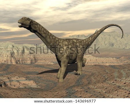 Big argentinosaurus dinosaur walking in the rocky desert by cloudy day - stock photo