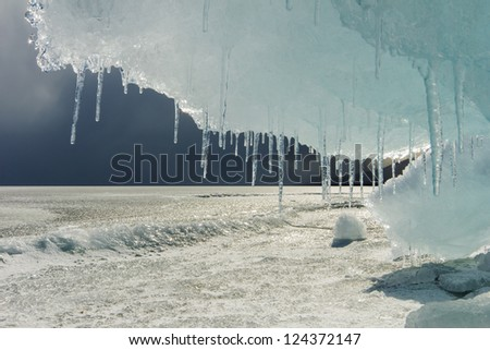 Big beautiful ice floe with icicles in the foreground on Baikal. Russia. - stock photo