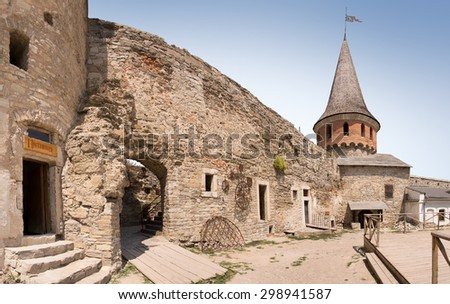 Big beautiful romantic court of known century strong defensive bulwark city place. Touristic showplace of Kamenetz-Podilskyi. Vintage panoramic view with space for text on blue sky background - stock photo