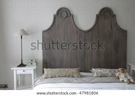 big bed with high headboard in gray color - stock photo