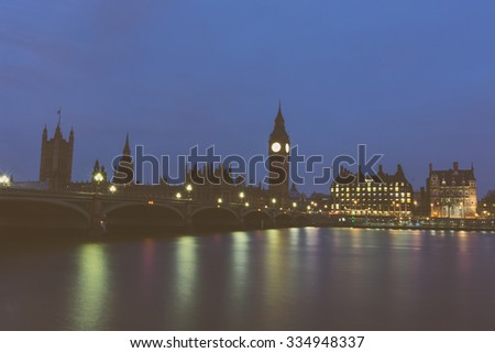 Big Ben and Parliament building at dawn in London with Westminster bridge and Thames river in foreground. Dark vintage noire edit. - stock photo