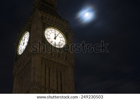 Big Ben in London, UK after midnight as the moon is high above in the background. - stock photo