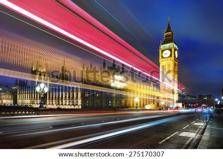 Big Ben, one of the most prominent symbols of both London and England, as shown at night along with the lights of the cars passing  - stock photo