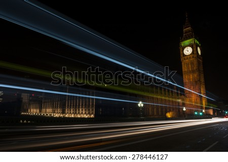 Big Ben, one of the most prominent symbols of both London and England, as shown at night along with the lights of the cars passing by - stock photo