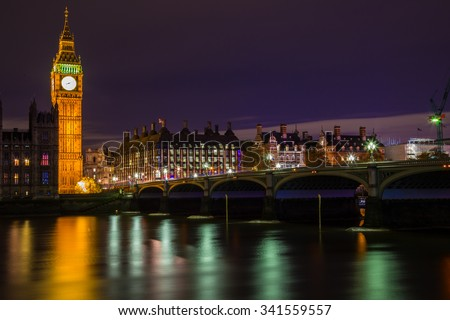 Big ben tower at night time with colorful street lighting from thames river and westminster bridge - stock photo