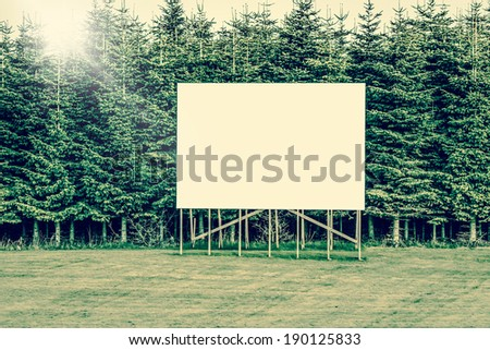 Big billboard sign surrounded by trees - stock photo