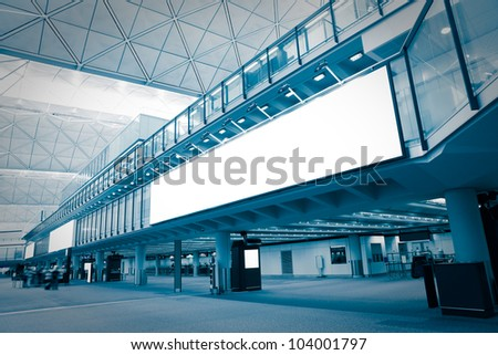 big Blank Billboard in airport with moving blurred passenger, blue tune, shot in asia - stock photo