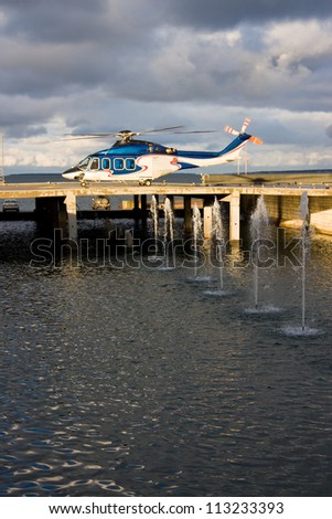 Big blue passenger helicopter waiting to take off from the platform behind fountains - stock photo