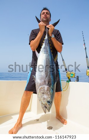 big Bluefin tuna catch by fisherman on boat trolling posing on deck - stock photo
