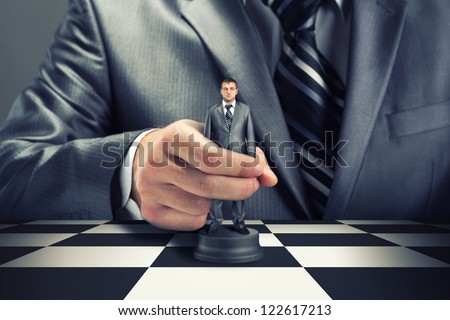 Big boss playing chess using businessman - stock photo