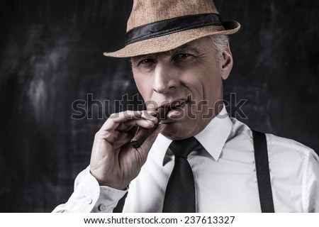 Big boss. Serious senior man in hat and suspenders smoking cigar and looking at you while standing against dark background  - stock photo