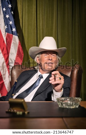 Big boss with white cowboy hat smoking cigar sitting behind desk. American flag in the background. - stock photo