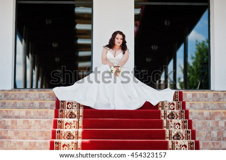 Big breasts brunette bride with wedding bouquet posed at wedding hall on the red carpet - stock photo