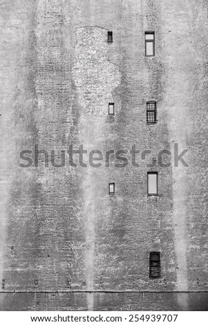 big brick wall of the old building of gray color with the damaged plaster and with small windows - stock photo