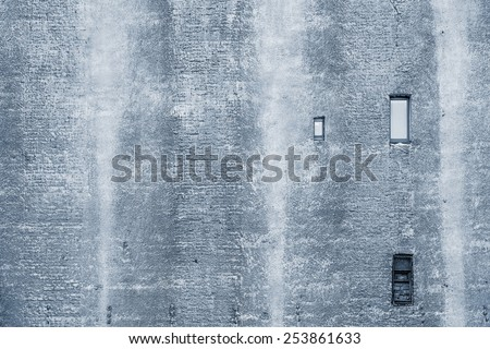 big brick wall of the old building of silvery color with the damaged plaster and with small windows - stock photo