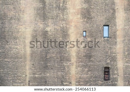 big brick wall of the old building with the damaged plaster and with small windows - stock photo