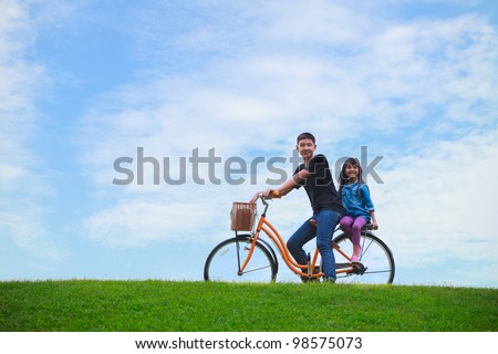 Big brother and young sister with bicycle - stock photo