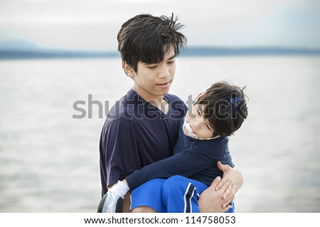 Big brother carrying disabled boy on beach by water. Child has cerebral palsy - stock photo