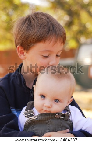 Big brother kissing his little brother on the head at a farm - stock photo