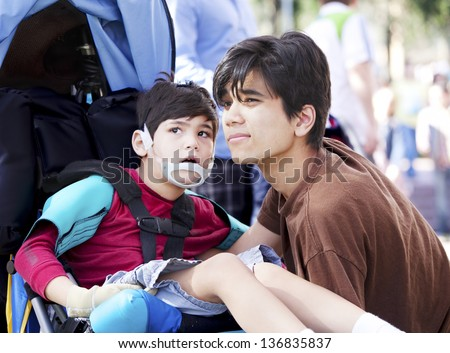 Big brother taking care of disabled little boy in wheelchair outdoors. Child has cerebral palsy. - stock photo