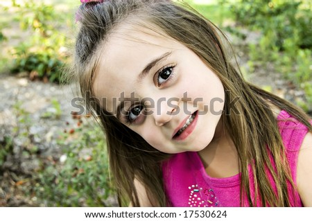 Big Brown eyes, closeup, and a beautiful child dressed in pink with long brunette hair. - stock photo