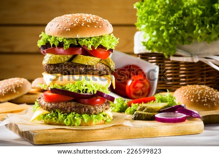 Big burger on the wooden table - stock photo