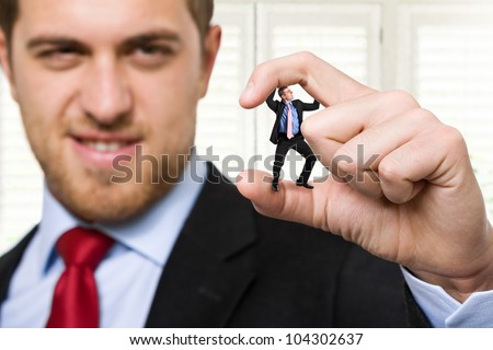 Big businessman crushing a small one - stock photo