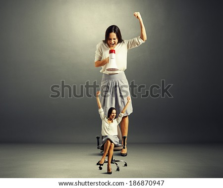 big businesswoman screaming at small happy woman over dark background - stock photo