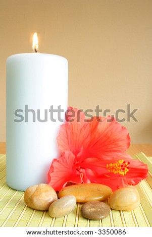 Big candle, flowers and pebbles on a mat - stock photo