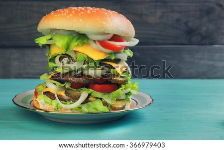 Big cheeseburger deluxe high on green wooden background in rustic style for gluttons - stock photo