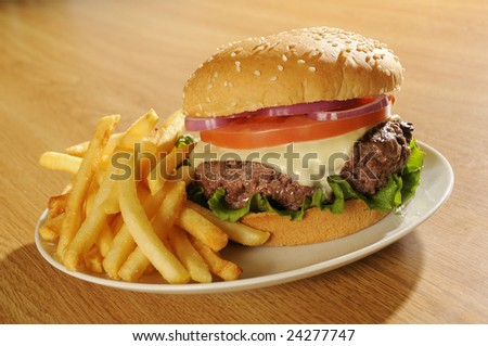 Big cheeseburger on white plate with french fries. - stock photo