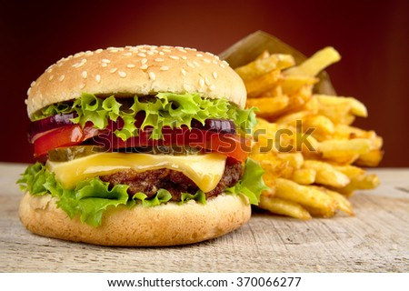 Big cheeseburger with french fries in bag paper on wooden table on red dpotlight background - stock photo