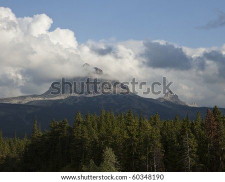 Big Chief Mountain in Glacier National Park on a day when it is surrounded by a halo of clouds. The mountain is a granite monolith that rises by itself in a corner of the park. - stock photo