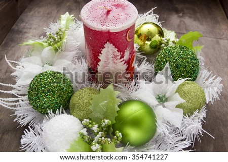 Big Christmas candle and festive wreath of white and green balls. - stock photo