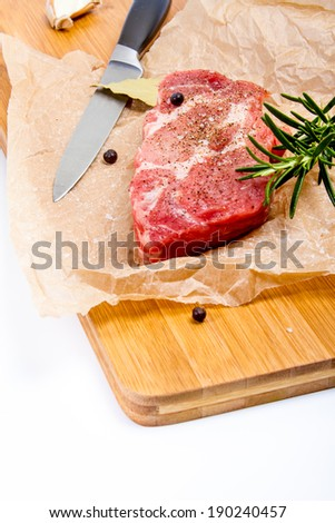 Big chunk of fresh meat on the brown cooking paper. Seasoned with rosemary and pepper. - stock photo