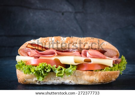 Big ciabatta sandwich with meat and cheese on dark background  - stock photo
