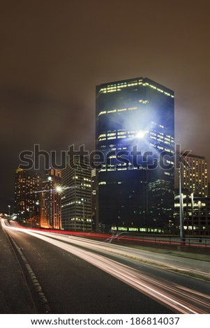 big city express way twilight time blurred cars passing by with illuminated CBD skyscrapers in the background - stock photo