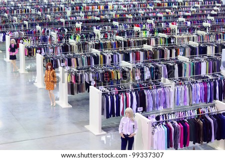 Big clothing store, dummies and many rows with hangers, variety of sizes - stock photo
